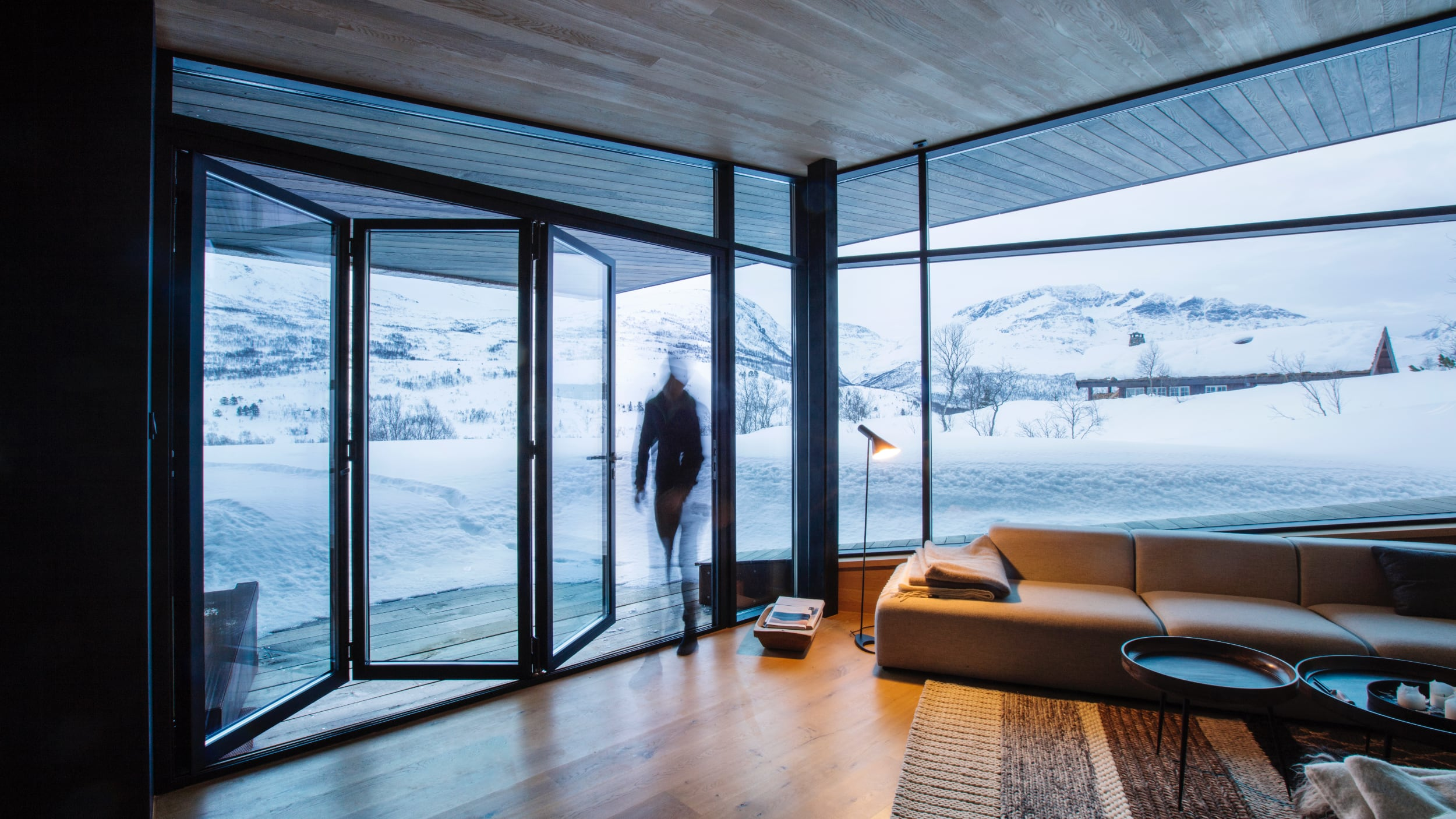 Store foldedører i glass åpner hytta opp til snødekkede fjell