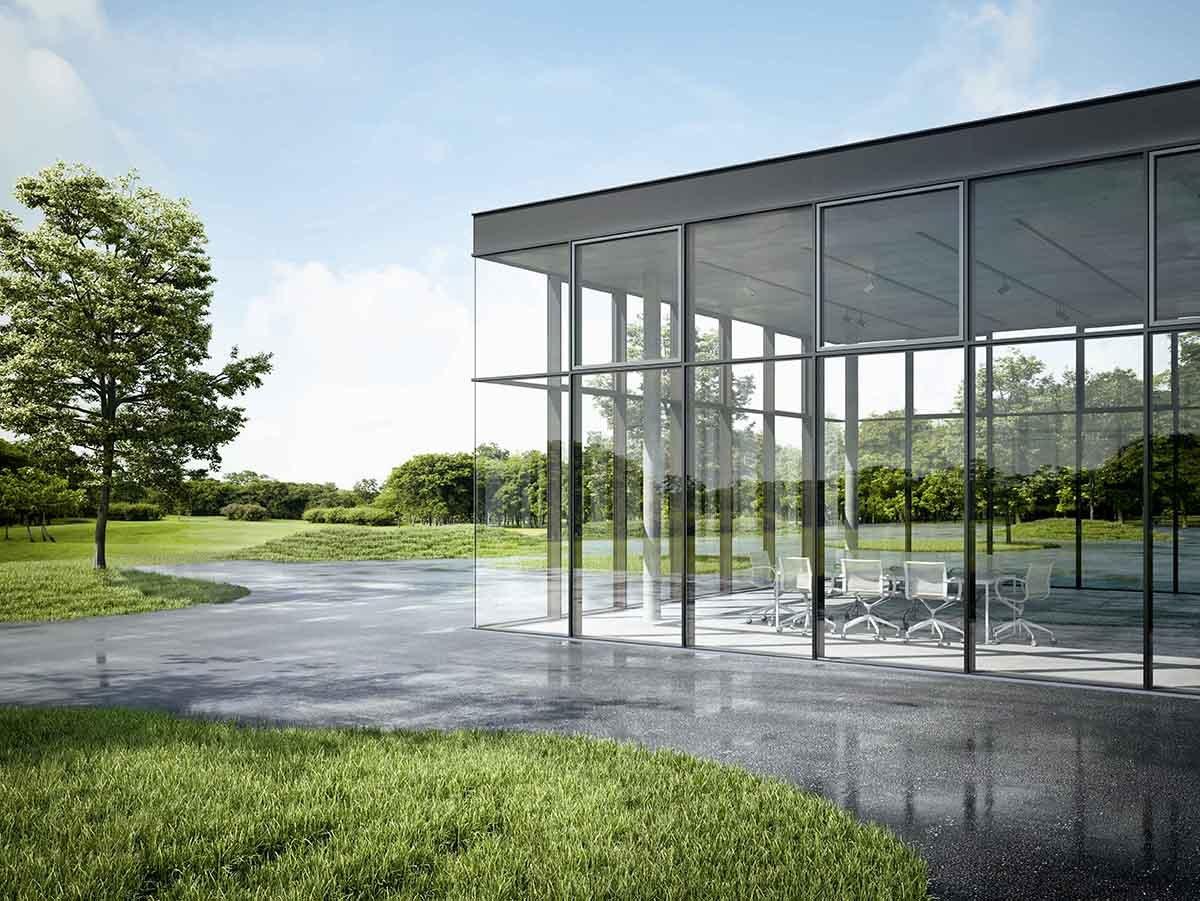 Bygg med glassfasade sett utenfra i en park