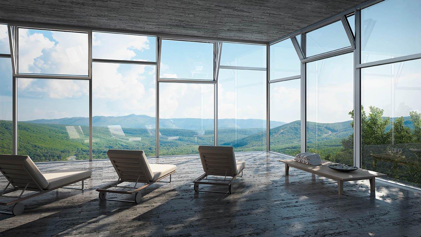Utsikt over fjell gjennom glassfasade.