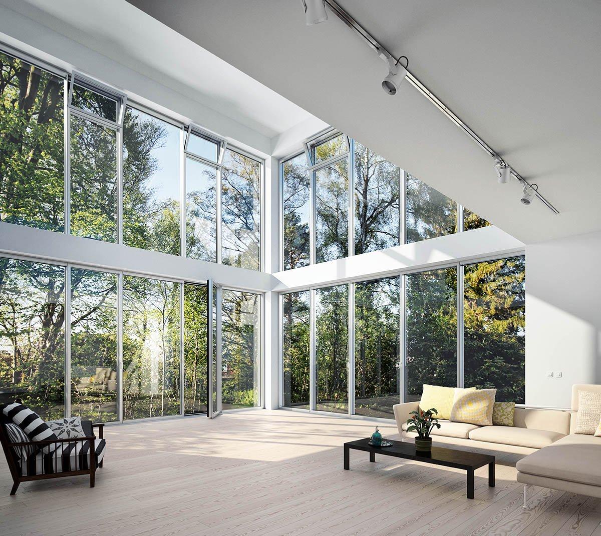 Glassfasade innenfra ser ut i løvskog.