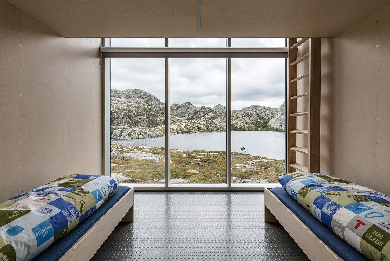 Soverom med utsikt gjennom store vinduer ut på fjellet