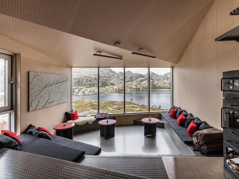 Interiør fra hytta med utsikt gjennom store glassvinduer