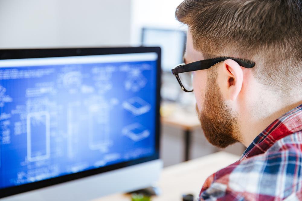 mann med skjegg og briller ser på en dataskjerm